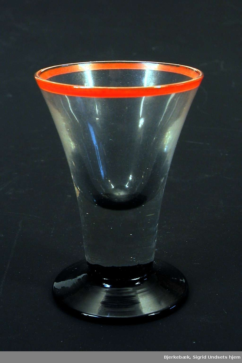 Drammeglass med sort fot og rød munningsrand.