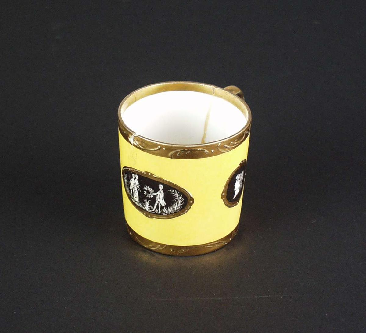 Mokkakopp, gul med forgylt og sort dekor. Innsiden er hvit. Stempelet er en N med en krone over. Stempelet er orange.