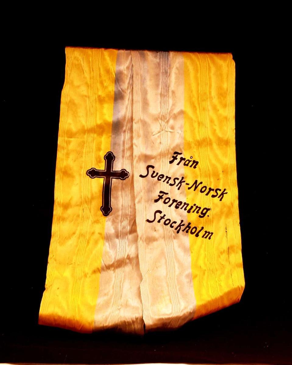 Bånd i gul og falmet blå silke. Båndet er delt i to. På det ene båndet står det: Från Svensk Norsk Forening. Stockholm. På det andre er det et sort kors.