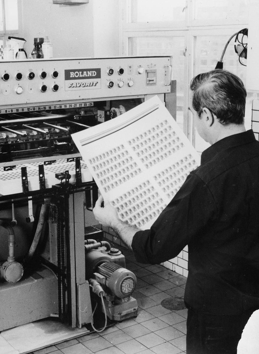 frimerketrykking, frimerkeproduksjon hos Emil Moestue A.S., Roland Favorit trykkemaskin, trykking i tofarget offsetmaskin, mann kontollerer trykkingen
