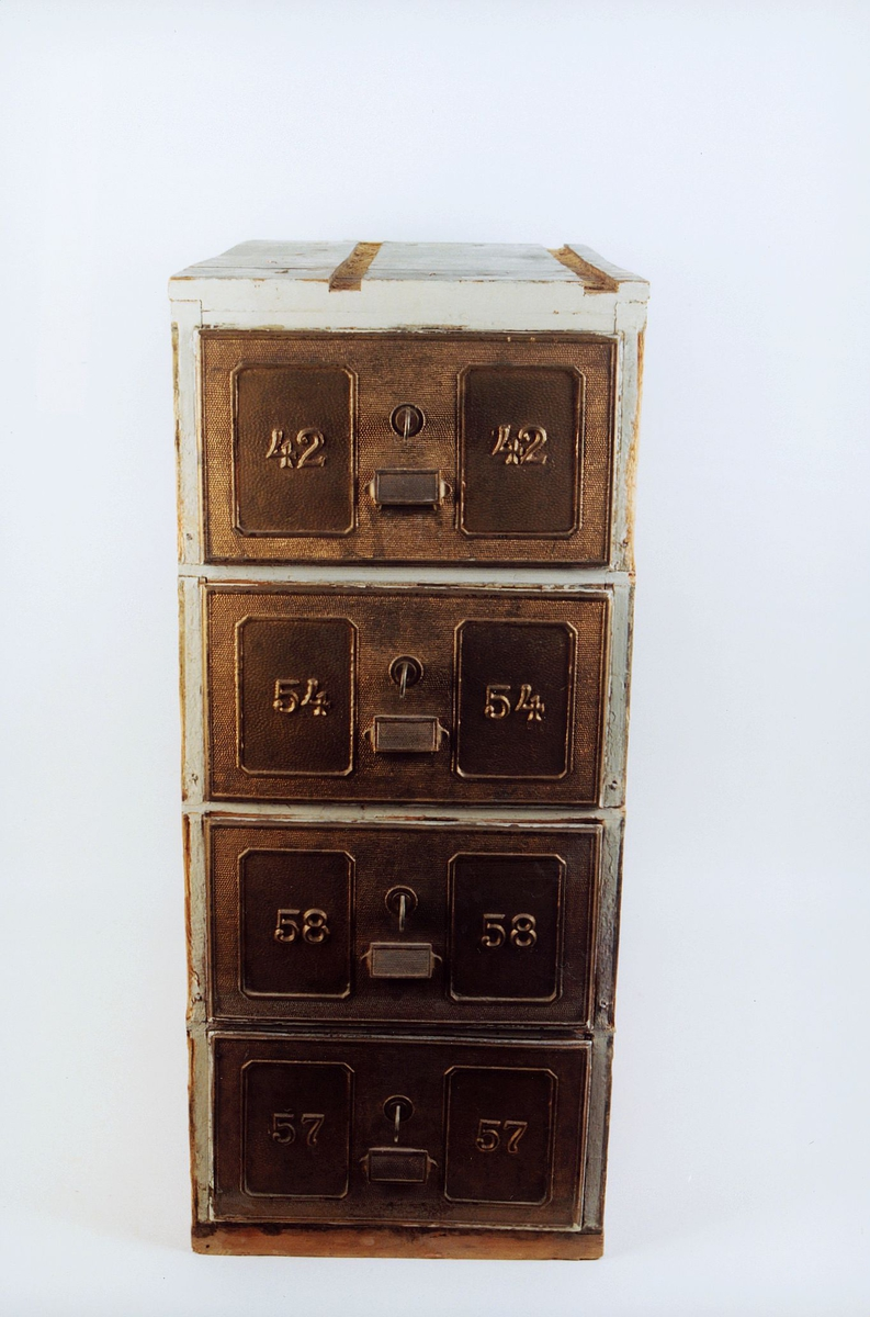Postboksanlegg i metall og treverk. Seksjon med 4 postbokser. Metallfargede nummererte og låsbare dører.