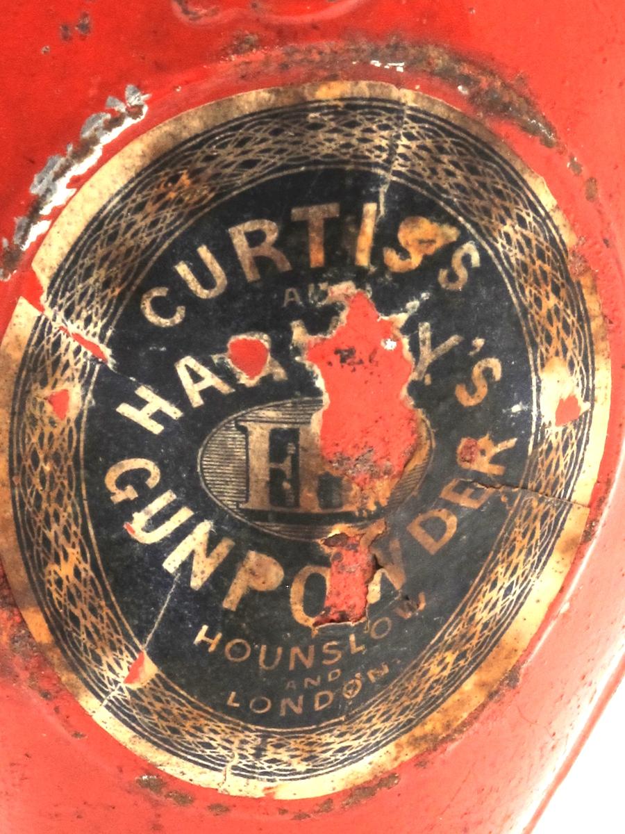 Kruttflaske,   Curtis and Harveyts Gun powder.   Hounslow and London.  Slutten 1800-årene. Blikk, rødmalt, i   Flat dråpeformet flaske med nedsenket  oval på hver side, hvor sort/hvit  papiretikett er limt på.  Lokk. på den smale munningen.  Tilstand: etikettene litt ødelagte.