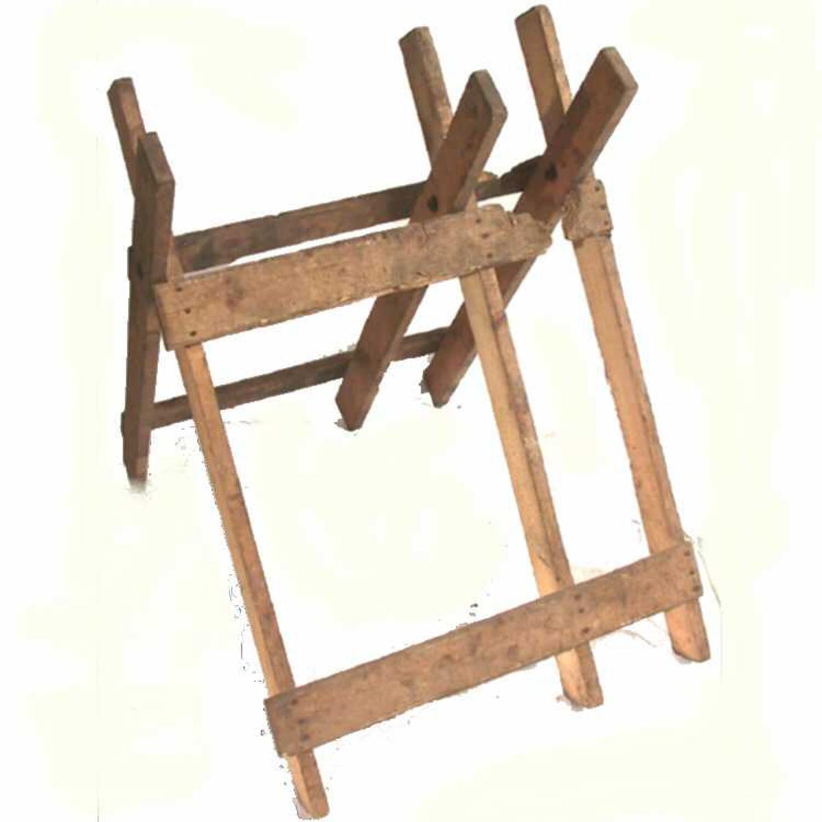 Sagkrakk med tre kryss, forbundet m liggende bord. Spinkel konstruksjon.