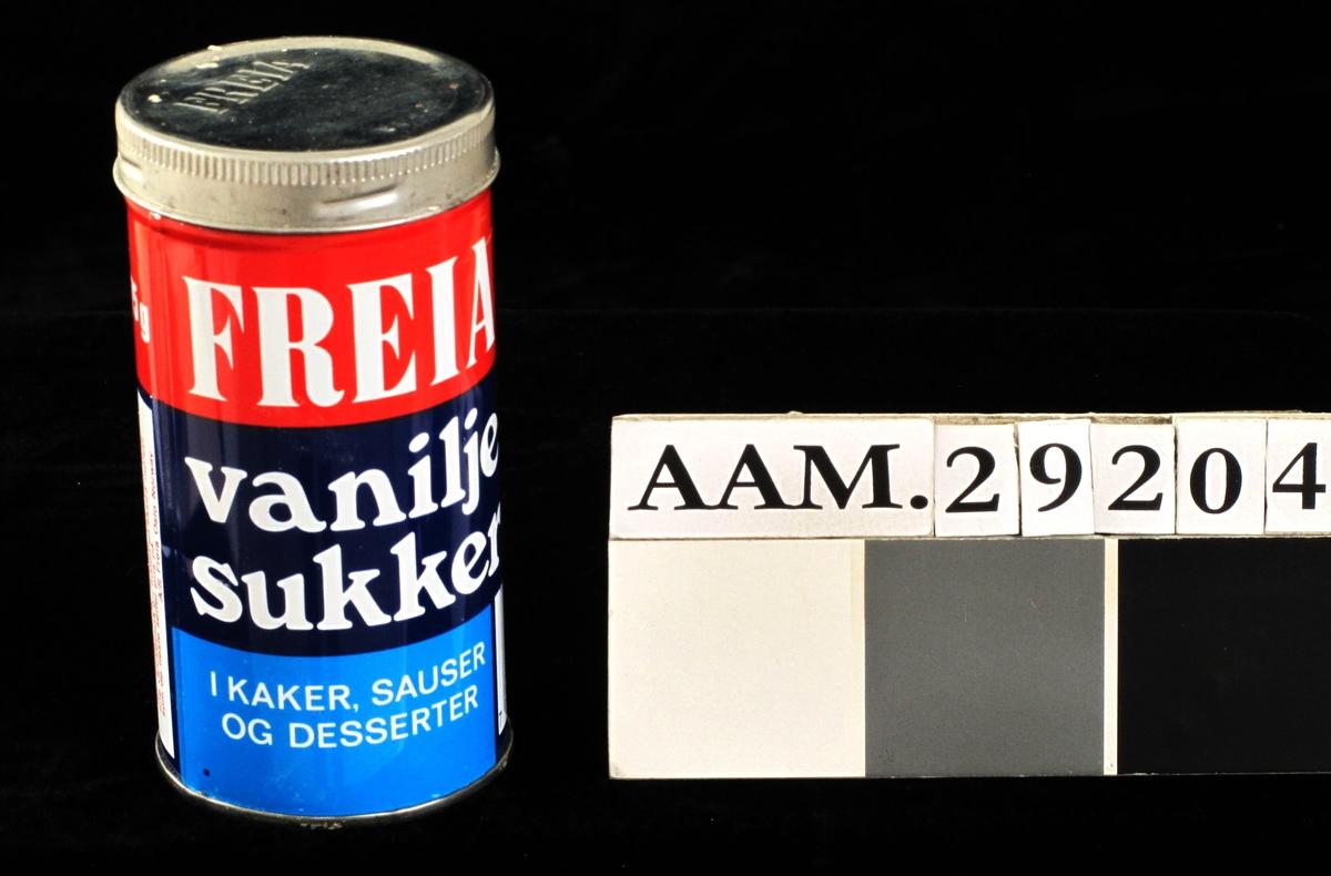 Rund blikkboks med skrulokk. I sterke farger: Rødt, og blått i mørk og lys farge. Varefalta og strekkode er trykt på boksen. Boksen var forsynt med papirforsegling under metallokket.Tilstand god.