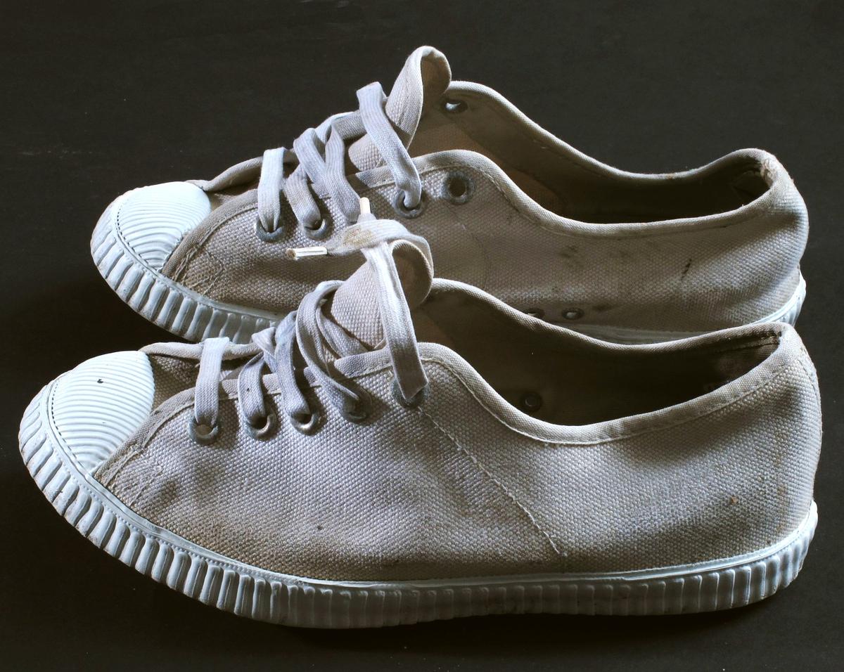 Hvite tennissko.  Gummisåle og tåforsterkning, Lerret overdel og hvite lisser gjennom fem par hull.  Rågummi såler med bølgemønster.  Tre luftehull på innsiden av skoen.  Slitt innside av hæl på begge skoene.