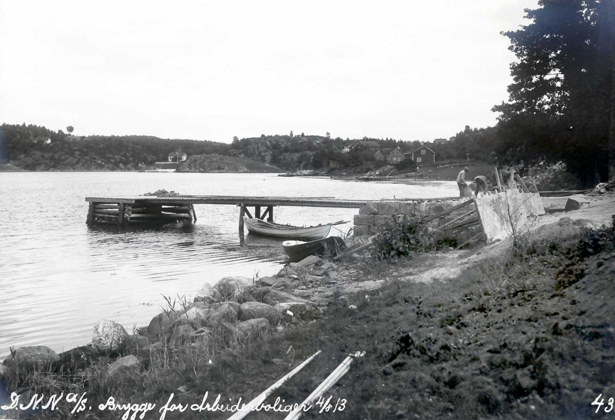 """""""04/08-1913"""" Eydehavn. Brygge for boliger i Nesgaten. Store mengder byggemateriale ble tatt i land på denne bryggen, og fraktet med hest og kjerre til byggeplassen (til høyre, utenfor bildekant). Neskilen og Helle til venstre. Snekkenes i bakgrunnen. Her kom bruforbindelse i 1921."""