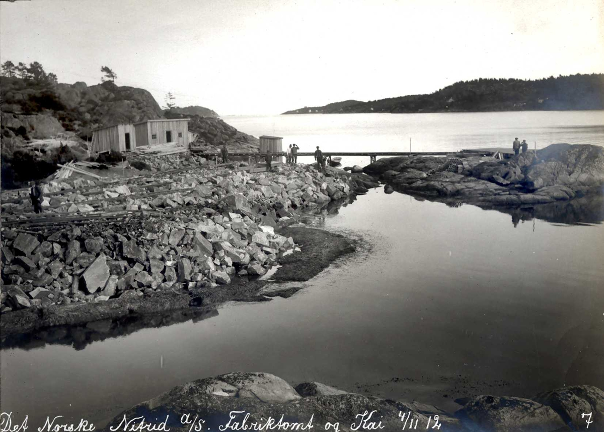 """""""04/11-1912"""" Nitriden. Utsprengte masser fra tomtearbeidene fylles i sjøen og ut til et skjær. Anleggsbrakker. Tromøysund og Tromøy til høyre."""