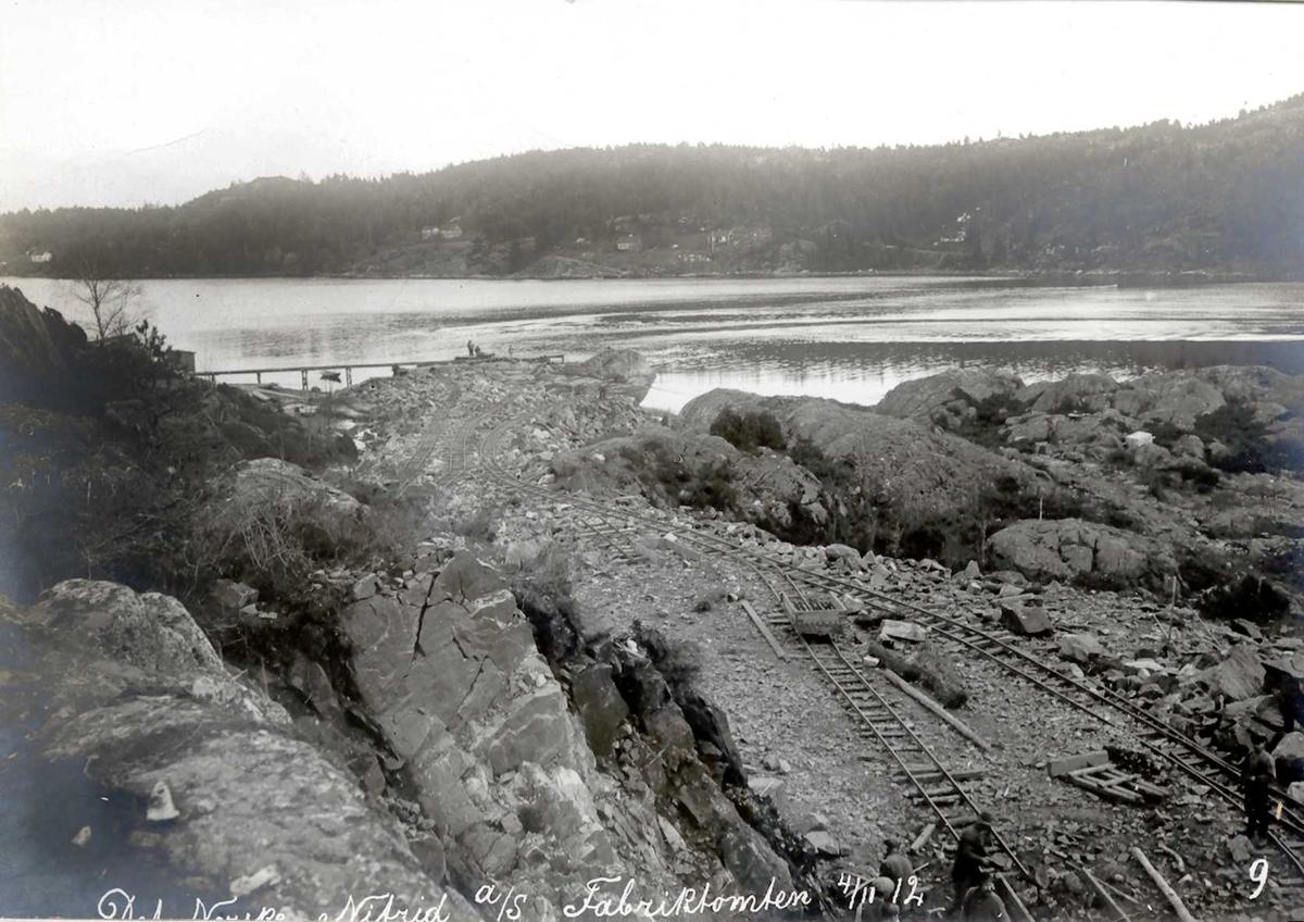 """""""04/11-1912"""" Nitriden. Fabrikktomten fylles ut og planeres av utsprengte fjellmasser. Skinnegang og traller for bortkjøring av stein. Tromøysund og Tromøy i bakgrunnen."""