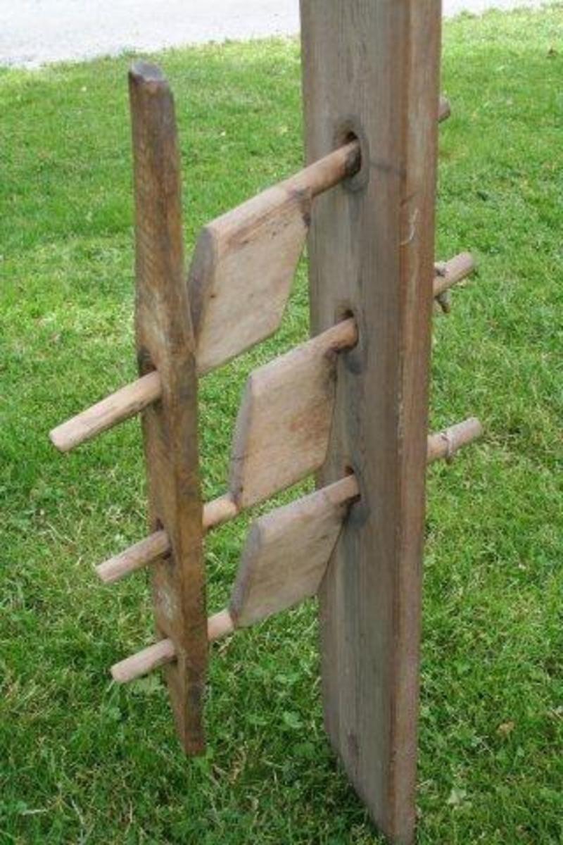 """Flat planke med tre sveiver forbundet med flatt håndtak. Et hull i hver ende av planken. Meget enkelt form for reiptvinne; kordellene festes til trepluggene ytterst på veivene. Veivene beveges samtidig vha. håndtaket som er montert på dem. Spor etter at """"aksling""""-hullene i planken har vært smurt med tjære."""