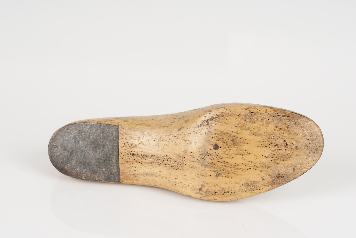 En tremodell i to deler; lest og overlest. Venstrefot i skostørrelse 40, med 8,5 cm i vidde. Hælstykket av metall. Lestekam i skinn.
