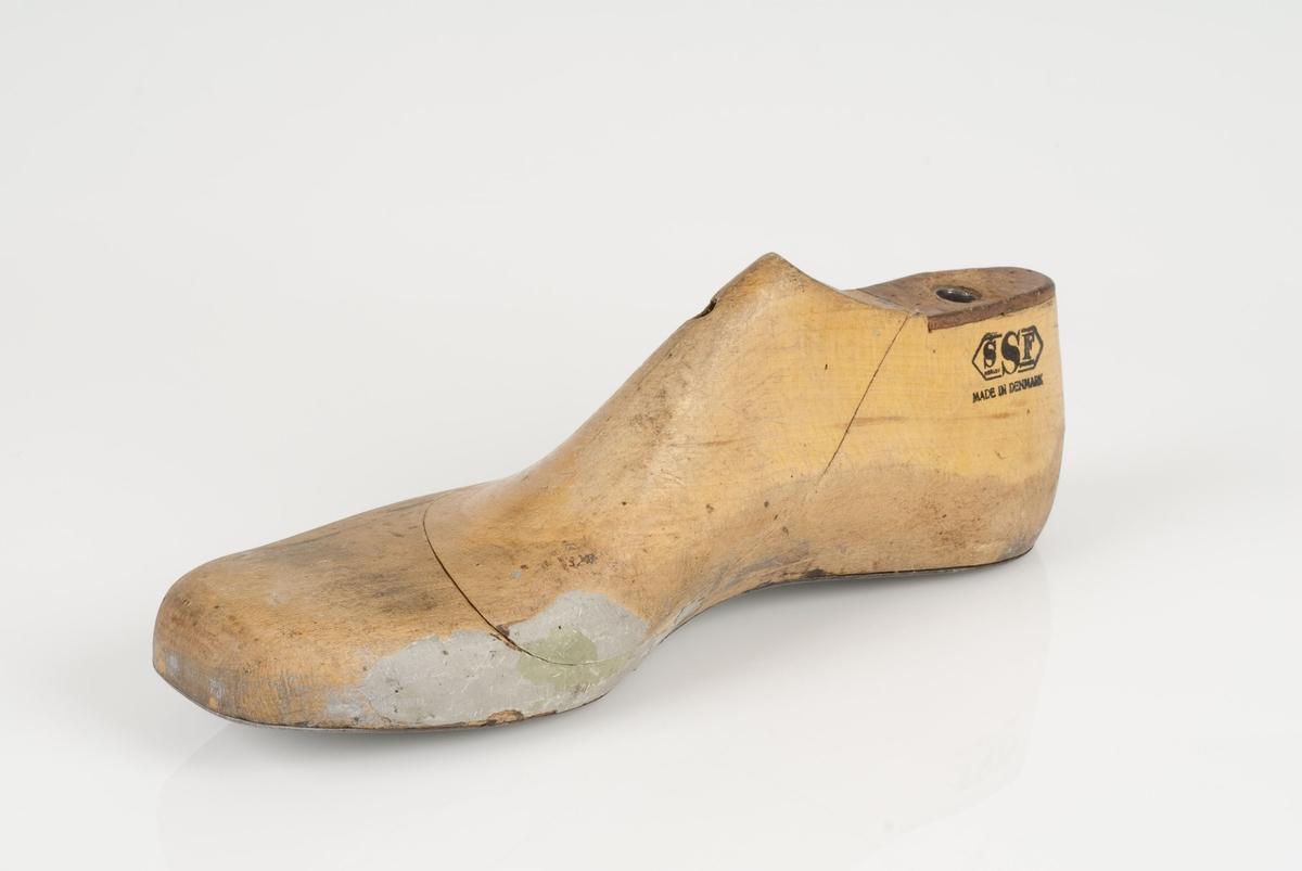 En tremodell i to deler; lest og opplest/overlest (kile). Høyrefot i skostørrelse 46, og 8 cm i vidde. Såle i metall. Lestekam i skinn.