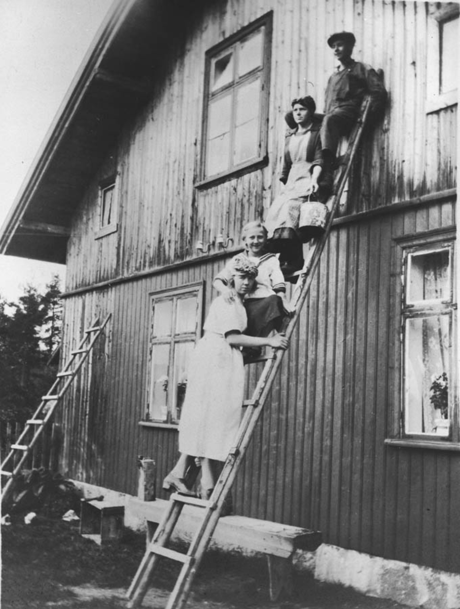 Personer på stige foran Høibraaten-huset