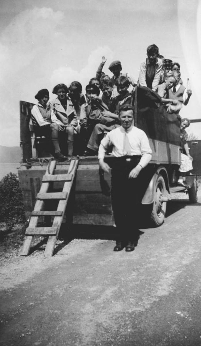 5. klasse på tur med Anders Hveem. Elevene sitter på lastebilens plan.