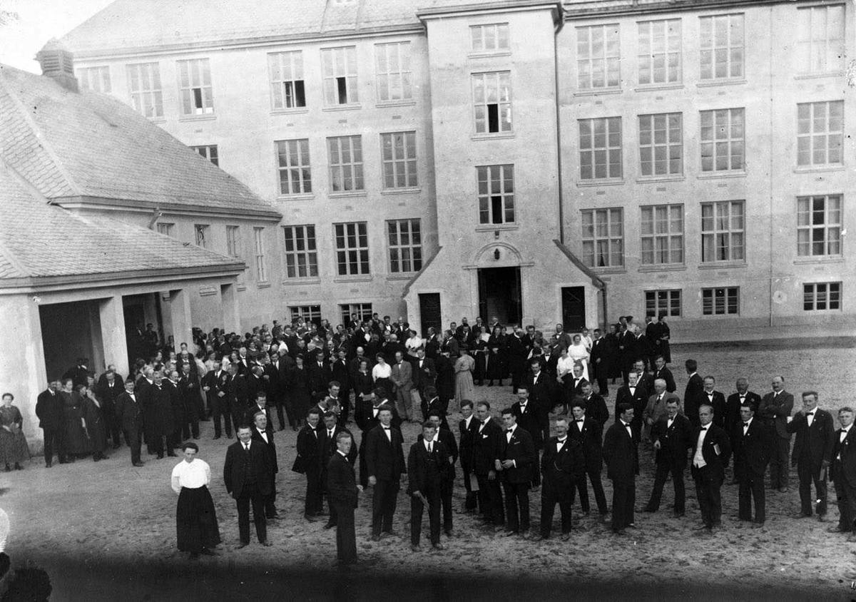 Volla Skole Forsamling i skolegården, og innvielsesfest i gymsalen. Stående i midtgangen i gymsalen skolestyrets formann Hagbart Bratli.