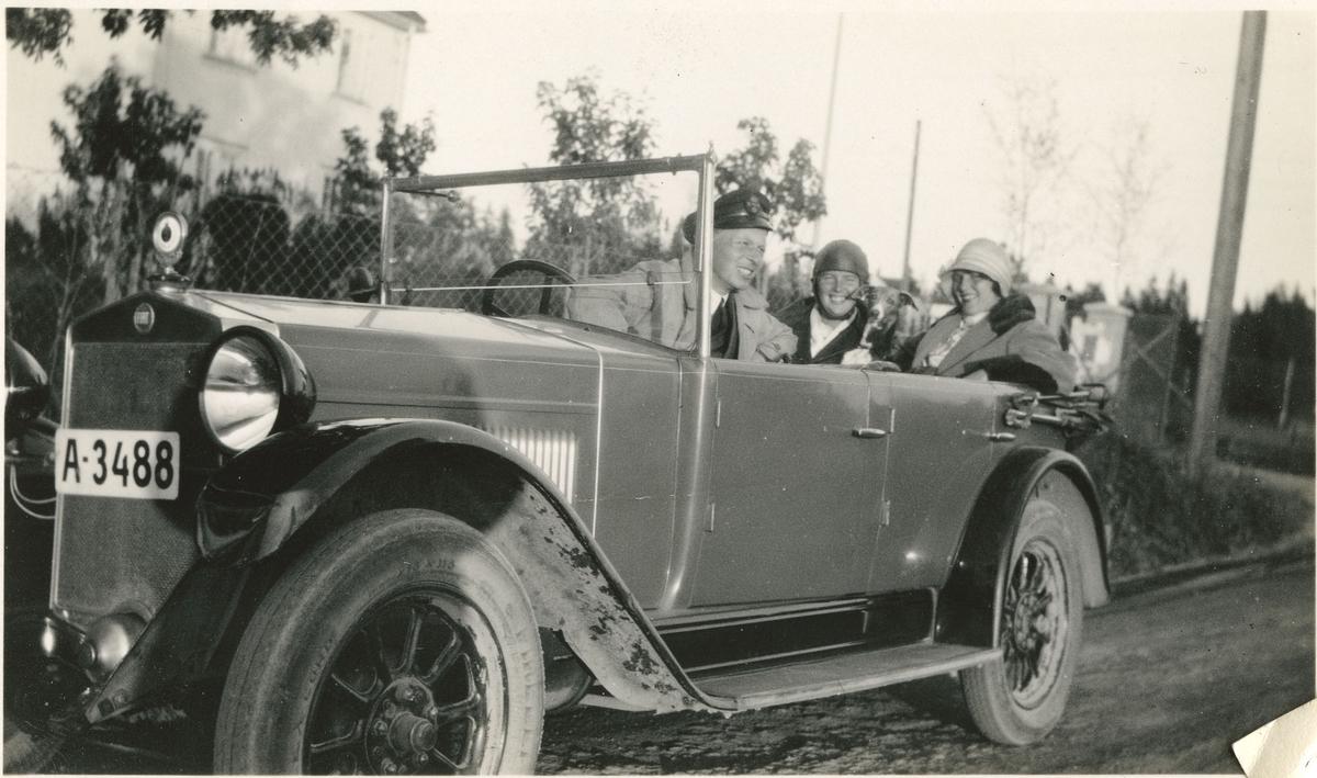 En mann og to damer i bil.
