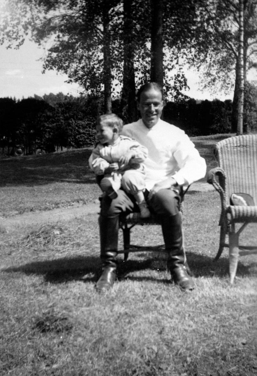 Far og sønn i stol i parken v/Sanitetslegens hus, Gardermoen