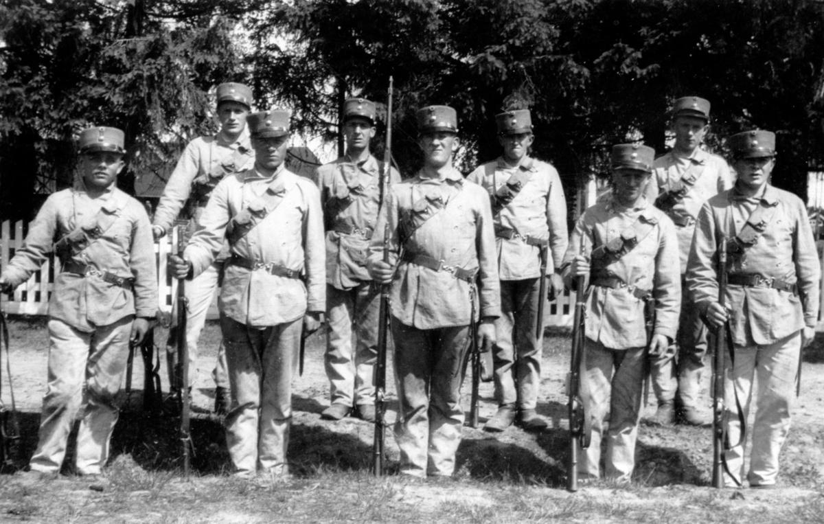 Soldater i arbeidsantrekk, oppstilt med gevær.