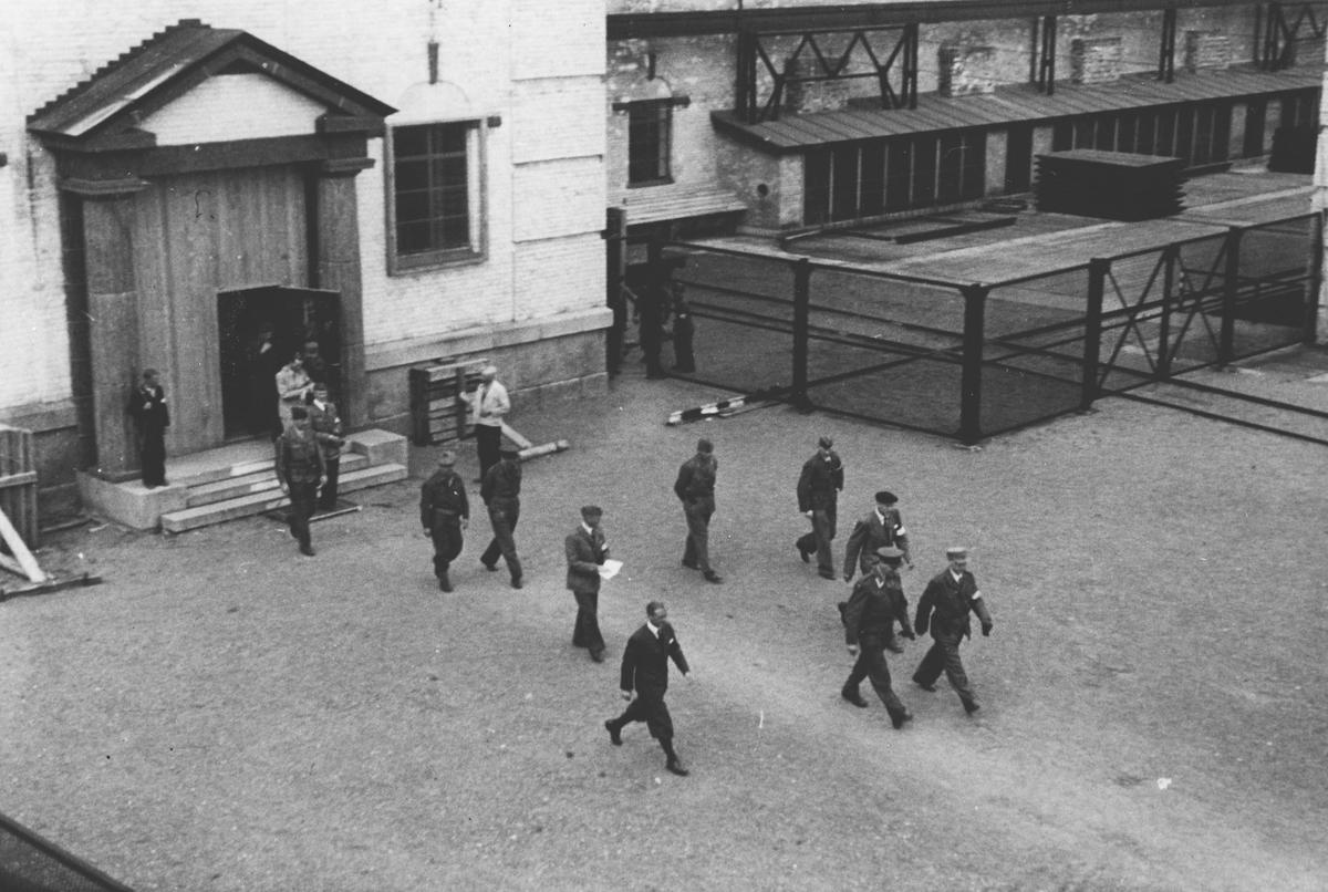 Fra frigjøringsdagene. Militære og sivile går over plassen foran hovedinngangen til Rånåsfoss kraftstasjon.