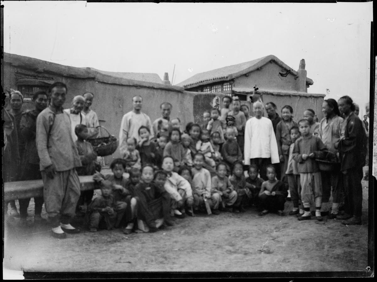 En gruppe mennesker av lokal befolkning foran en bygning.