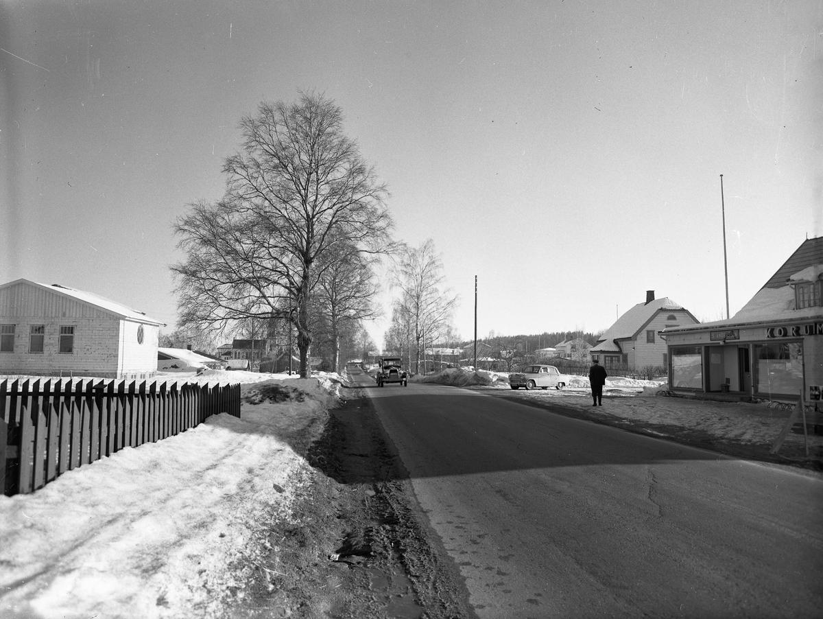 Råholt. Før- og etterkrigs biler. S Andersson KORUM.. står på forretningen til høyre. Menighetshuset til venstre. Kirken i bakgrunnen.