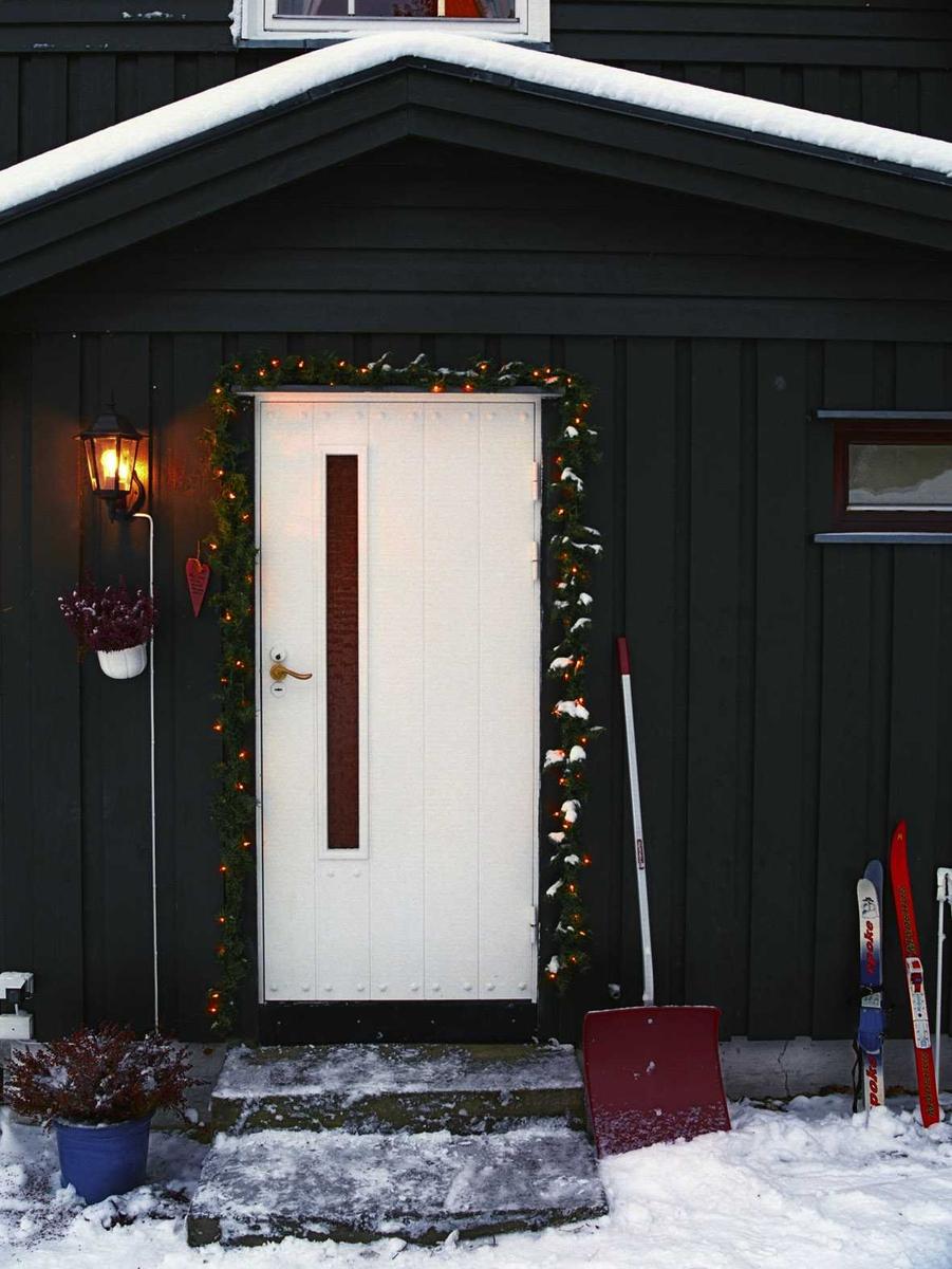 Julebelysning  Hvit julebelysning i girlander ved dørparti ved enebolig