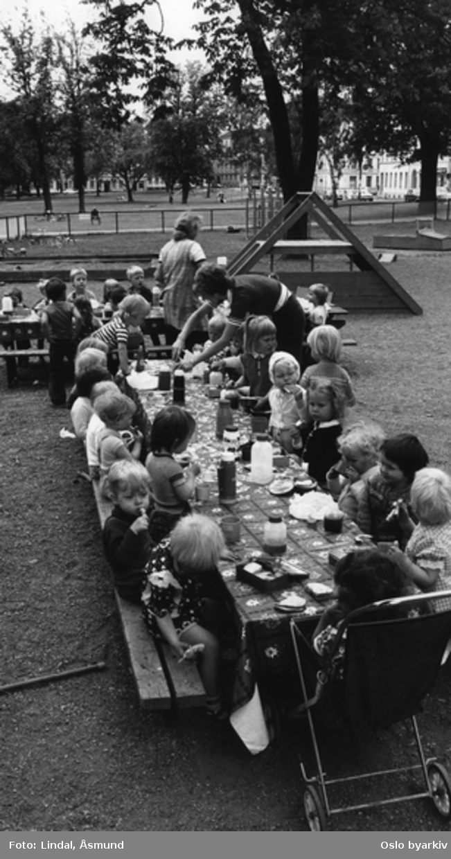 Barneparken i Sofienbergparken. Matpause ved langbord. Parktanter. Fotografiet er fra prosjektet og boka ''Oslo-bilder. En fotografisk dokumentasjon av bo og leveforhold i 1981 - 82''. Kontakt Samfoto ved ev. bestilling av kopier.