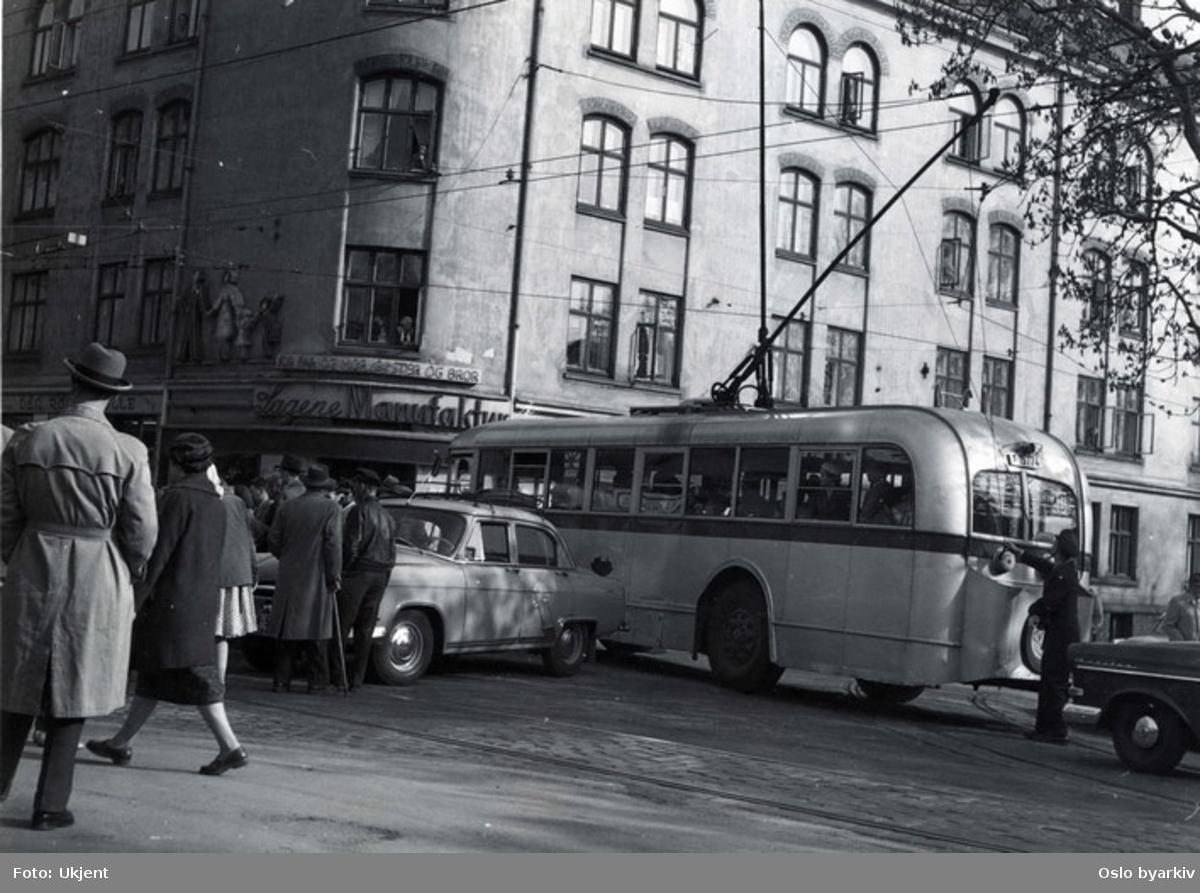 Oslo Sporveier, Trolleybuss i gatekryss på Sagene. Sagene Manufaktur på hjørnet, den Røde Mølle ved siden av. Sjåføren kontrollerer kabelen til strømkoblingen. På hjørnet av Arendalsgata og Grimstadgata.