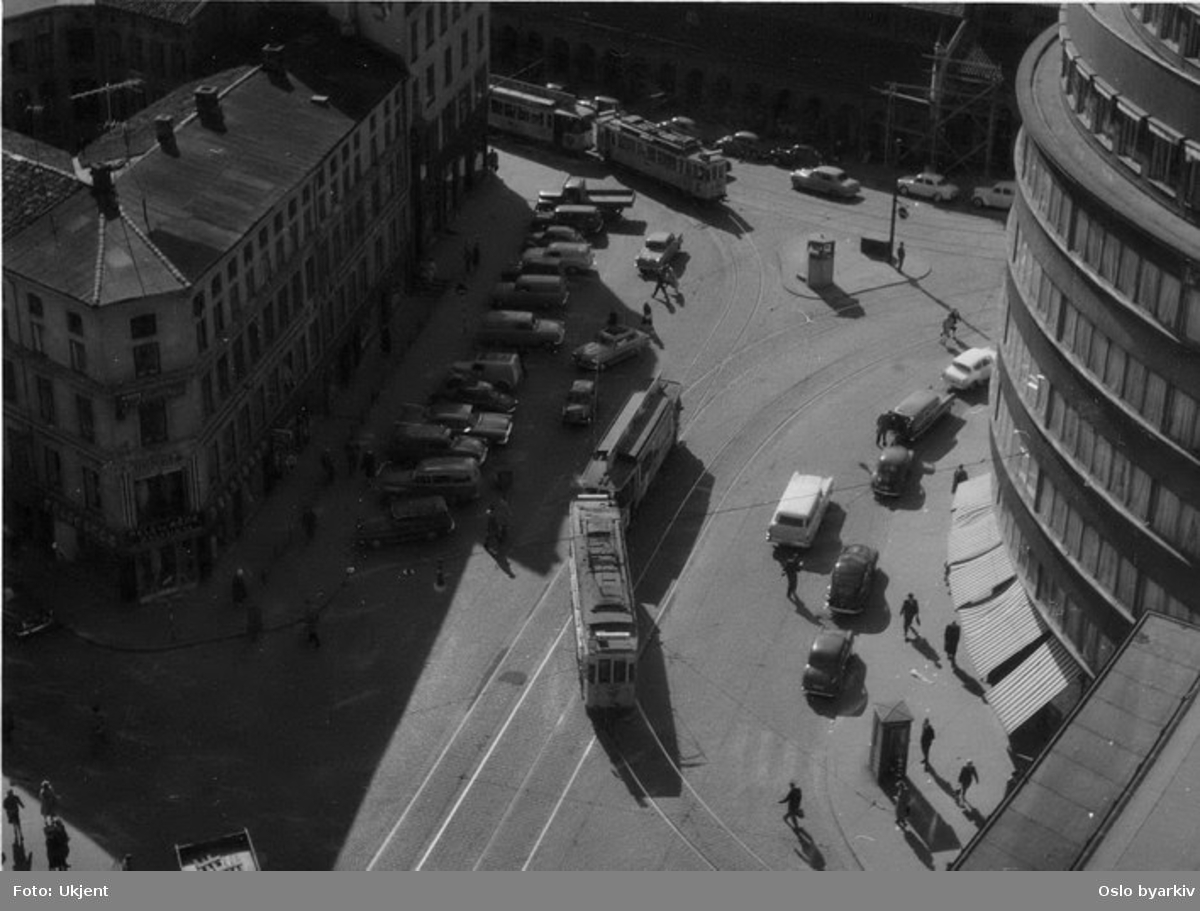 Oslo Sporveier. Trikk motorvogn 103 type SS lang med tilhenger svinger inn i Skippergata fra Gunnerus' gate. Gatebilde, bilparkering.