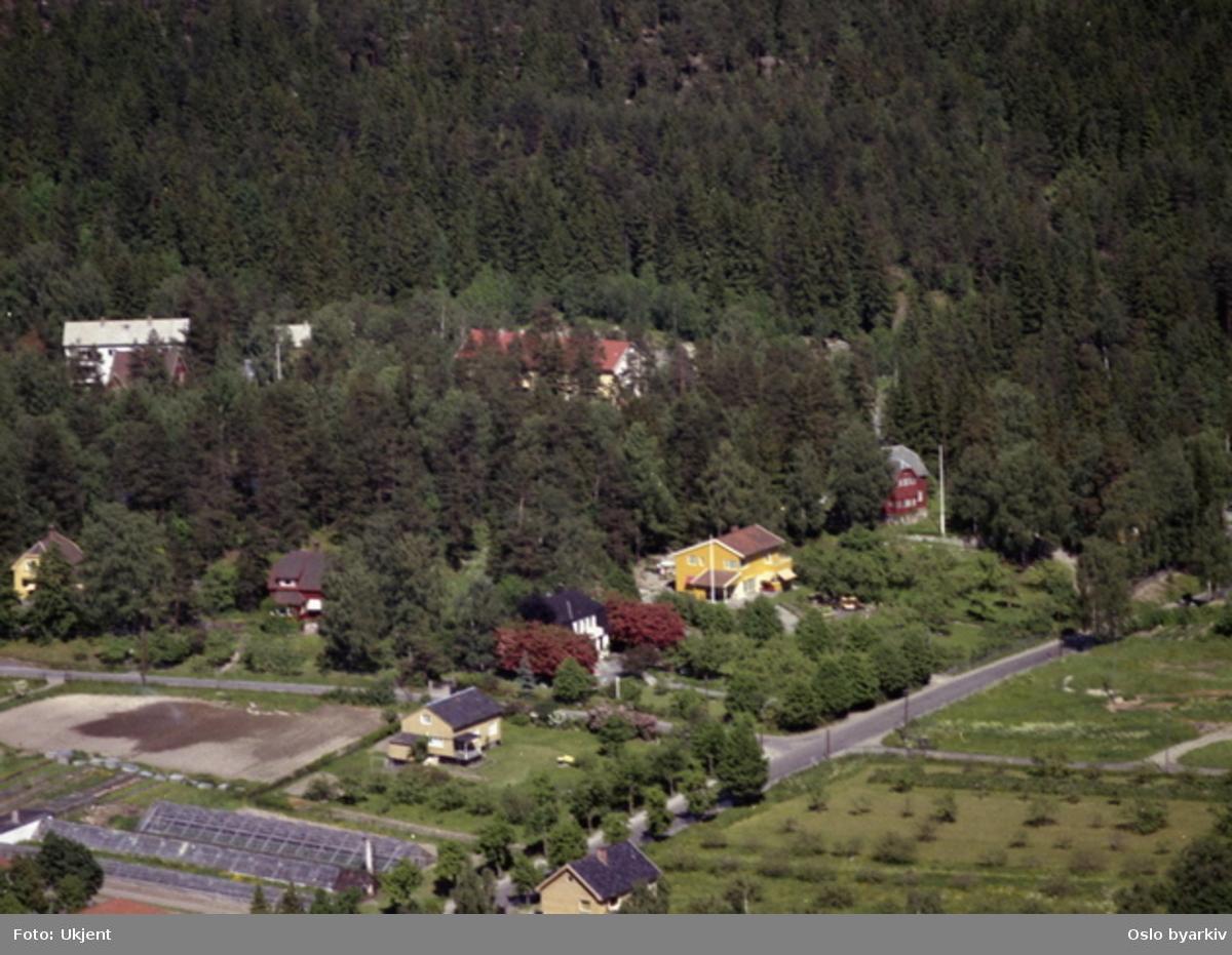 Det gule huset midt i bildet er Nordstrandveien 70A. Veien til venstre er Postdamveien. Husene bakenfor ligger i Kaptein Oppegårds vei. (Flyfoto)