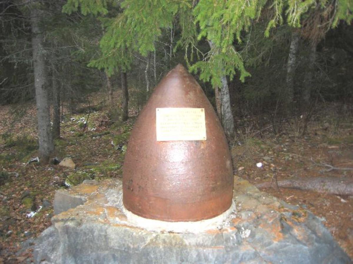 Bautastein med toppstykket av en tysk bombe festet på toppen. Metallplate med inskripsjon.
