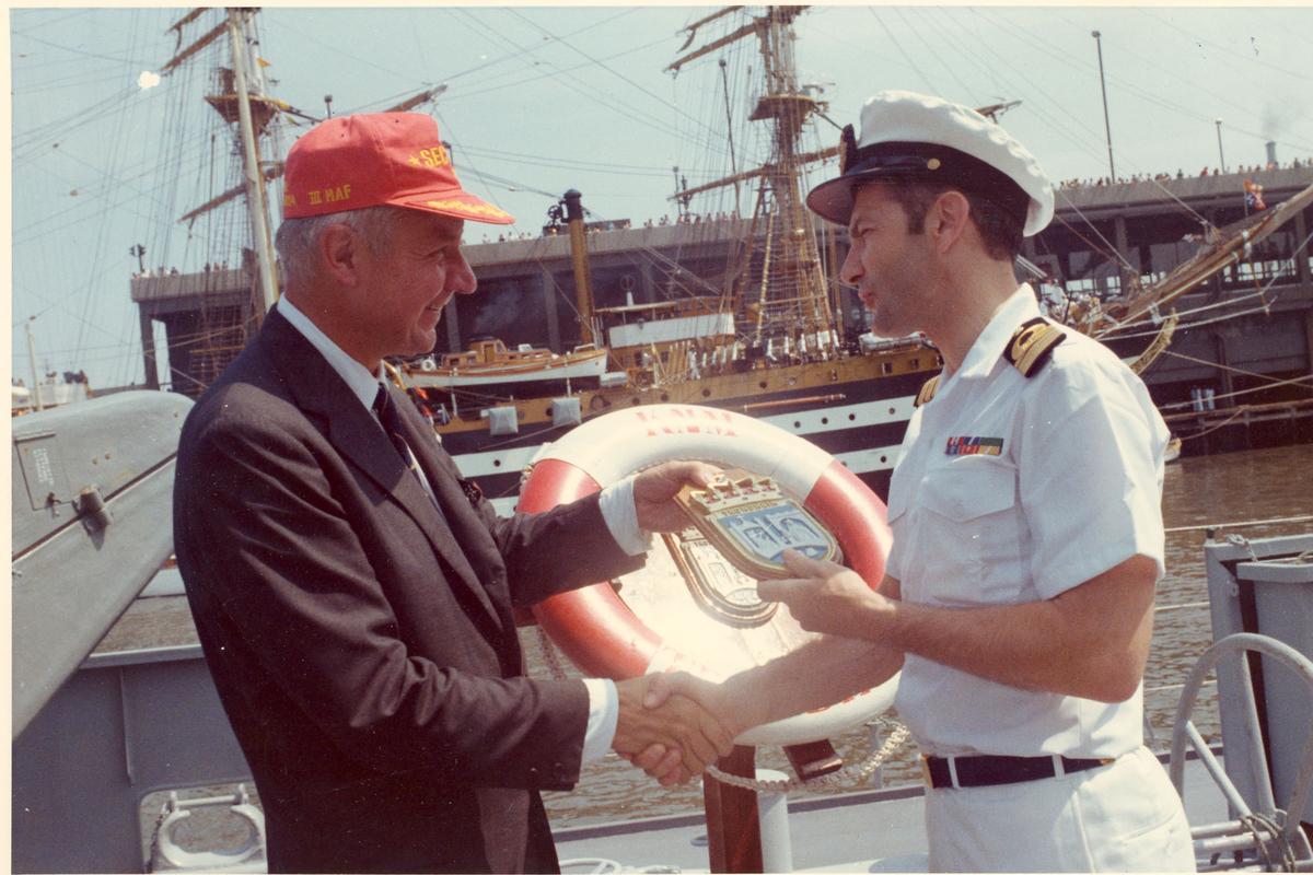 """Oslo-kl.- fregatt KNM """"Trondheim"""" får besøk av Secretary of the Navy J. W. Middeldorf i New York, sommeren 1976. Skipssjefen overrekker fartøyets crest  til Mr. Middeldorf."""