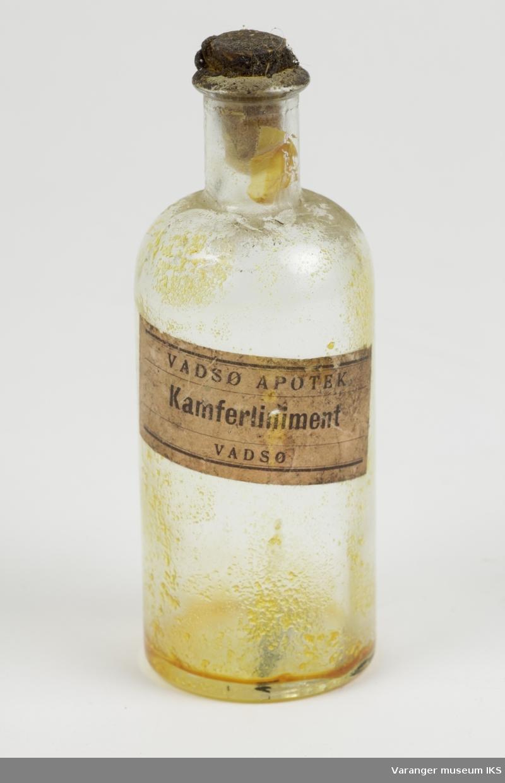 Liten medisinflaske med trekork. Inni flasken ses rester etter oransje innhold. Rødlig etikett med svart trykk.