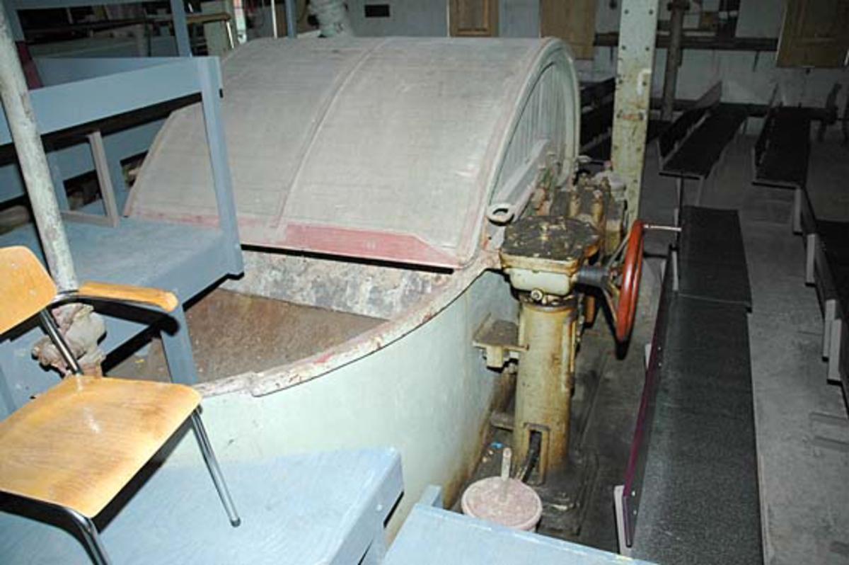Hollenderen ved Klevfos Cellulose- & Papirfabrikk i Løten i Hedmark.  Denne maskinen ble levert av Drammens Jernstøperi i 1910 og installert i forbindelse med at Klevfos-fabrikken ble gjenoppbygd etter brannen høsten 1909.    Hollenderen ble altså brukt til å blande og male papirmassen i.  Det dreier seg om et digert kar med en innvendig midtvegg, samt en valse (såkalt «kubbe») og et «grunnverk».  Ytterflatene på de roterende hollenderkubbene var besatt med skinner eller «kniver» av stål eller fosforbronse.  Disse maler mot det faststående grunnverket, som også har kniver av samme materiale.  Trykket kubben skulle ha mot grunnverket bestemte malegraden på papirmassen.  Dette trykket kunne justeres ved hjelp av det rødmalte rattet til høyre i bildet.  Malingsgraden (fibrilldannelsen) hadde stor betydning for papirkvaliteten.    Det blåmalte amfiet og stålrørstolen i forgrunnen står på dette stedet fordi at hollenderiet etter at Klevfos-fabrikken ble museum har vært brukt som teatersal for forestillingen «Arbesdaer».  Også benkene vi skimter til høyre i bakgrunnen er satt hit for å skaffe sitteplasser for publikummet til denne forestillingen. Ådalsbruk.