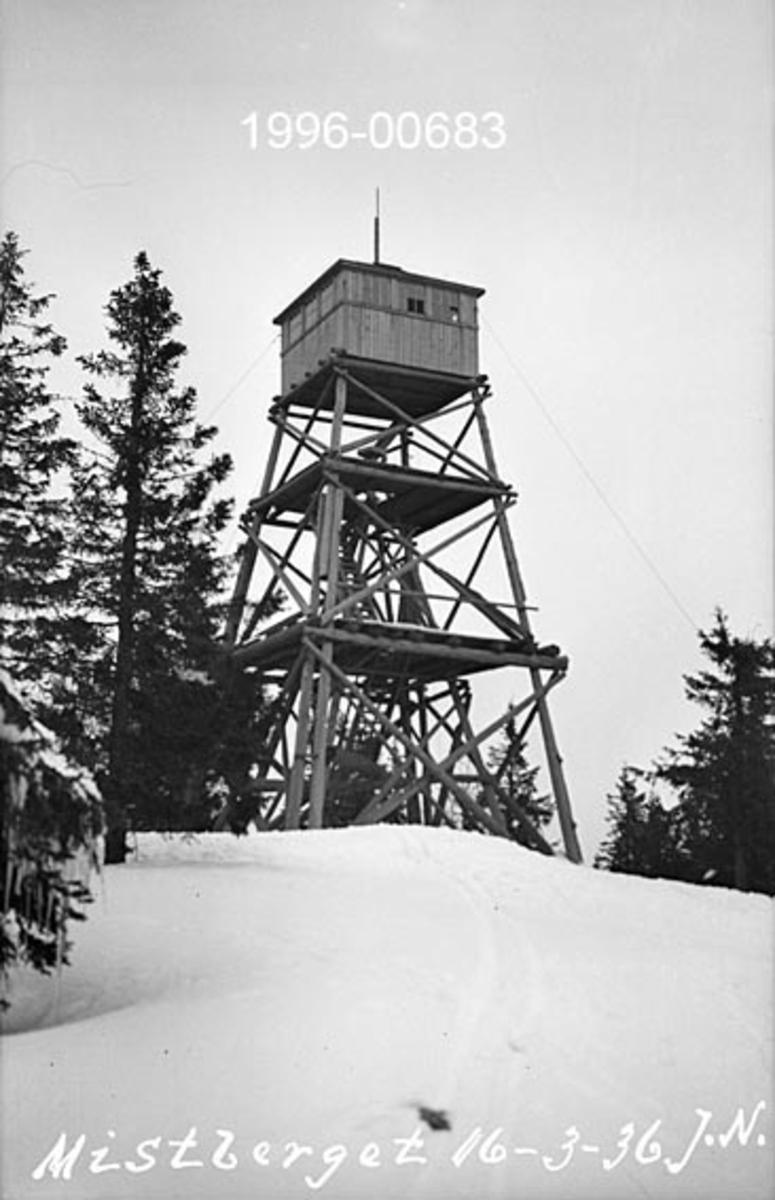 Tårnet på Mistberget skogbrannvaktstasjon 665 meter over havet i Eidsvoll kommune.  Dette tårnet ble reist i 1925 og erstattet av en ny konstruksjon i armert betong i 1938.  Fotografiet skal være tatt 16. mars 1936, altså mens det første tårnet ennå sto.   Fotografiet er tatt fra bakken, et steinkast fra tårnet.  Konstruksjonen har et noenlunde kvadratisk grunnplan, der fire par hjørnestolper som skråner inn mot tårnets midtakse er bærende elementer.  Fra omkring midten av tårnet er det bare en stolpe i hvert hjørne.  Konstruksjonen er avstivet med tømmerkryss i tre plan på alle fire sider.  På toppen av den åpne konstruksjonen er det bygd ei brannvakthytte i bordkledd bindingsverk, og med lynavleder på taket.  Adkomst til hytta skjedde ved hjelp av stiger som føres gjennom to plattformer og til slutt gjennom en lem i golvet på hytta.  Omkring tårnet vokste det spredte furutrær, men tårnet var såpass høyt at disse ikke hindret sikten.   De skogbrannforebyggende forskriftene for Eidsvoll kommune er gjengitt under fanen «Opplysninger», se spesielt § 9.