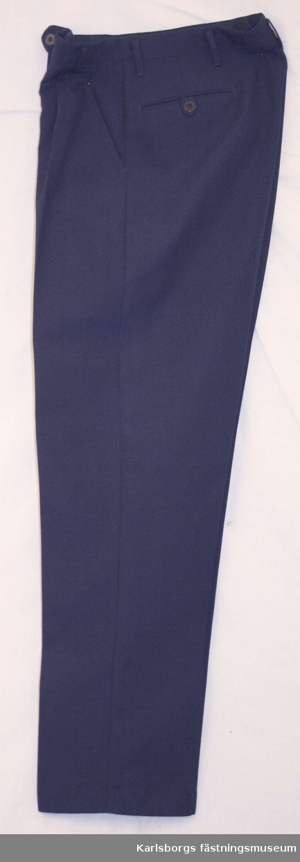 Storlek: C 46 Långbyxor m/1930 av mörkblått tyg. Löst midjeband med knapp o knapphål. Blixtlås i gylfen, sid- och bakfickor, varav de senare med knapp och knapphälla. Byxorna har hällor för livrem.