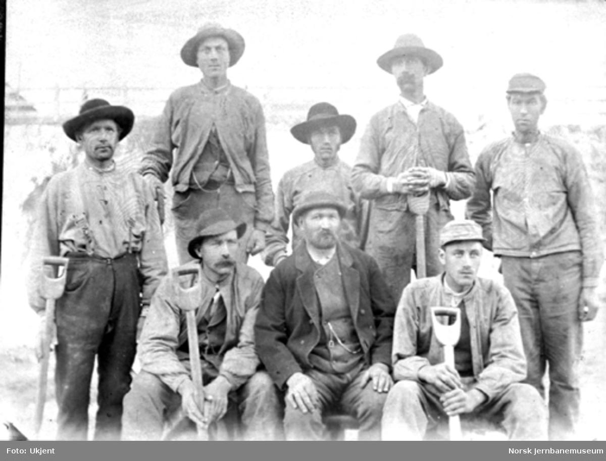 Gruppebilde av åtte anleggsarbeidere på Østfoldbanens østre linje ved Mysen stasjon
