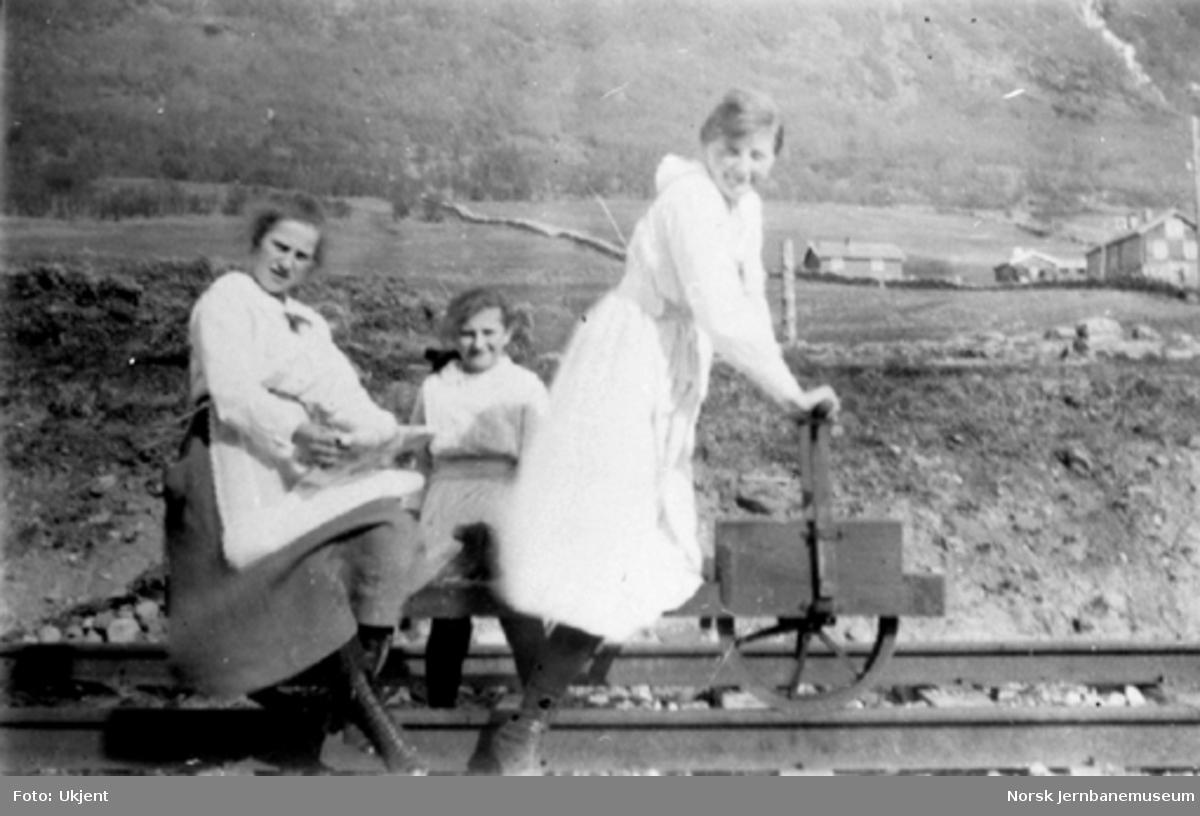 Tre damer poserer på en sparkedresin