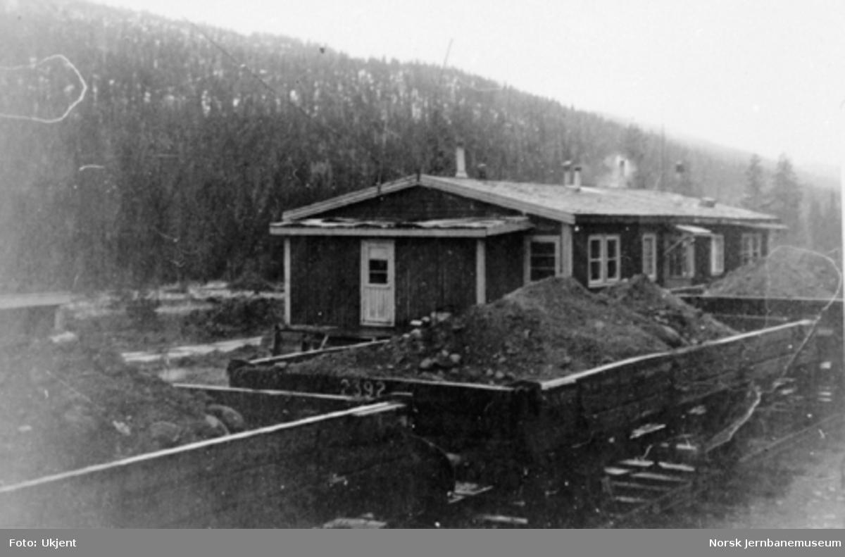 Ørtfjell provisoriske ekspedisjonshus med grusvogner i forgrunnen
