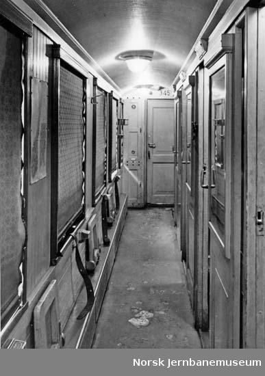 Interiørbilde fra sidegang i personvogn litra Co nr. 345; med eldre lysutstyr