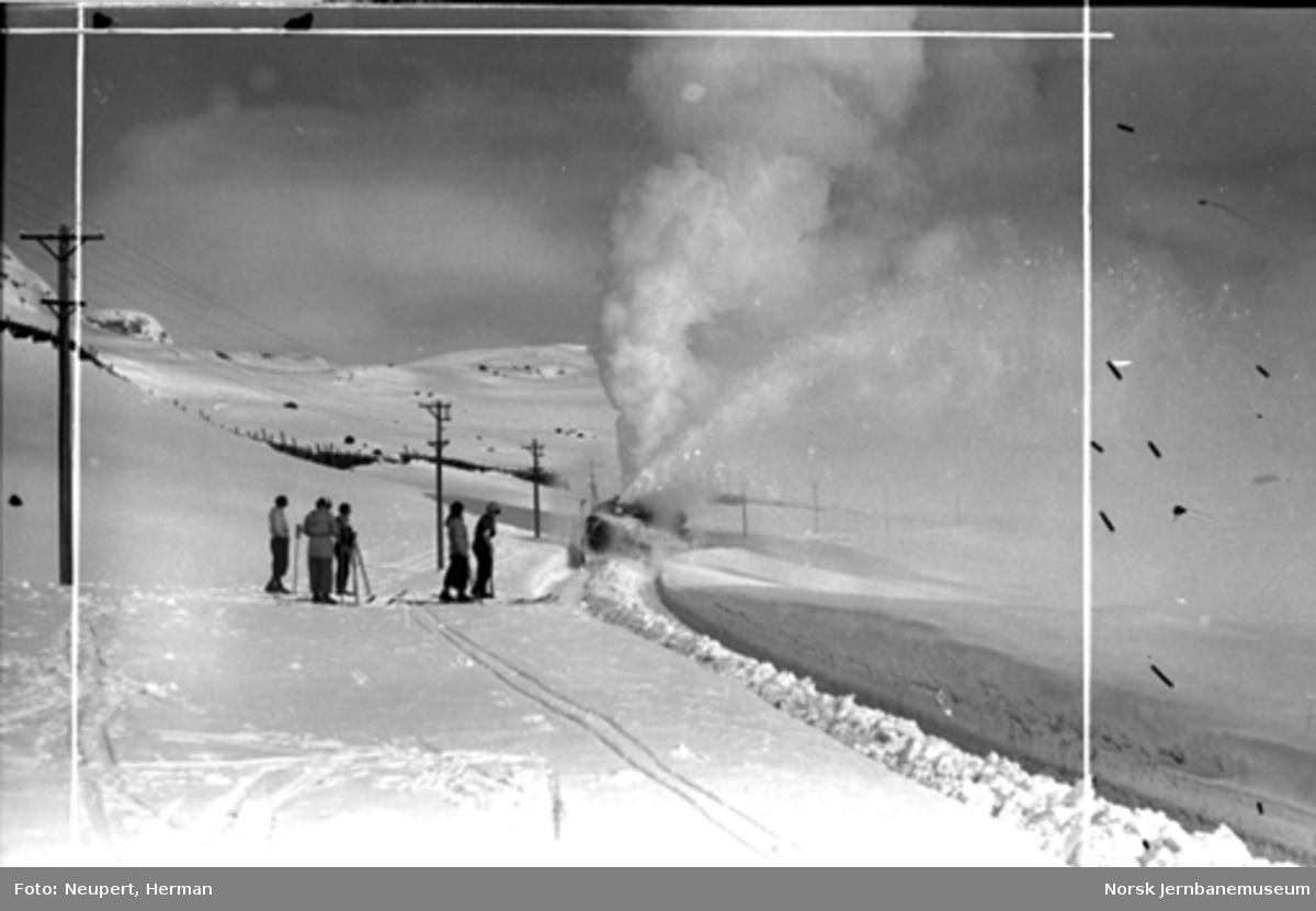 Skiløpere beundrer roterende snøplog i aksjon på Bergensbanen