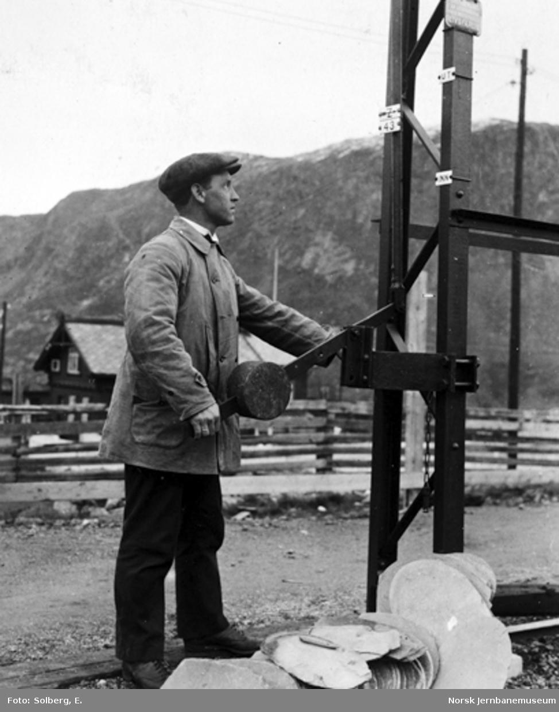 Ofotbanens elektrifisering : mann betjener håndtak for inn- og utkobling