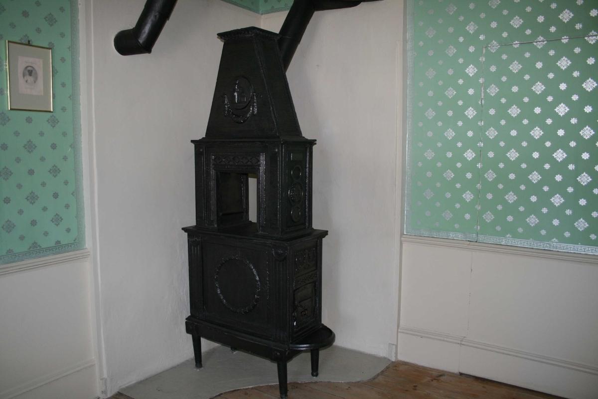 Gammel jernovn, Louis XVI stil. 2 etasjer m/pyramidetopp, kvinnefigur m/brennende alter i medaljong vase og krans.  Rosett i hjørner, står Eidsvold i medaljong, og CA på ovnsdøra.