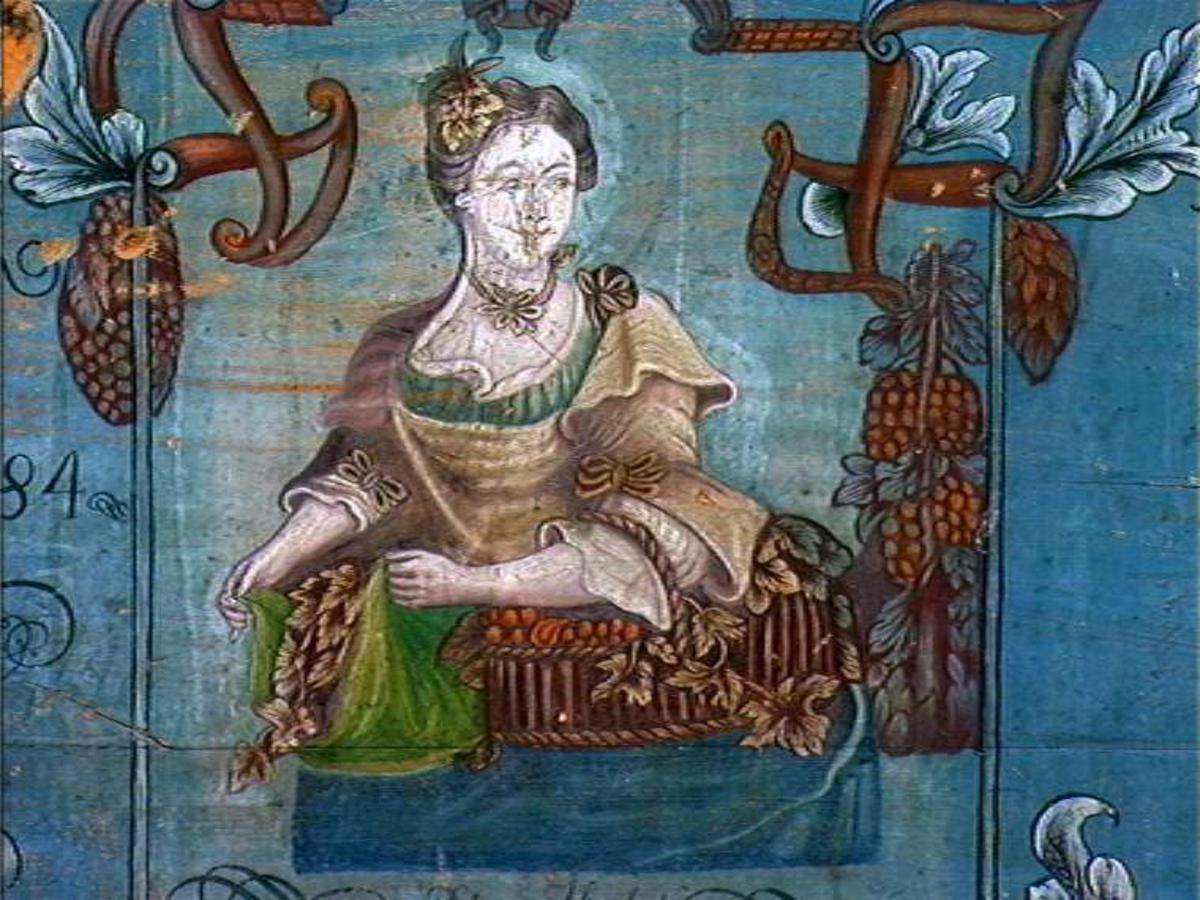 """Kisten er malt av Knut E. Horne (1763-1848) fra Oppdal, og dekorert med to allegoriske kvinnefigurer med blomster og kornbånd. De symboliserer """"Sommeren"""" og """"Høsten"""", og er antakelig malt etter forbilde fra et tysk mønsterstikk. Horne var sentral i utformingen av det lokale stilpreget i Oppdalsmalingen."""