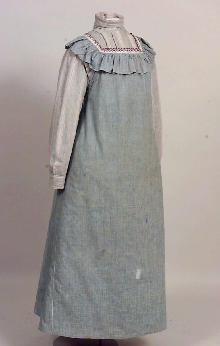 Blå og hvitt forkle med dekor av brodert maskinblonde og volange.