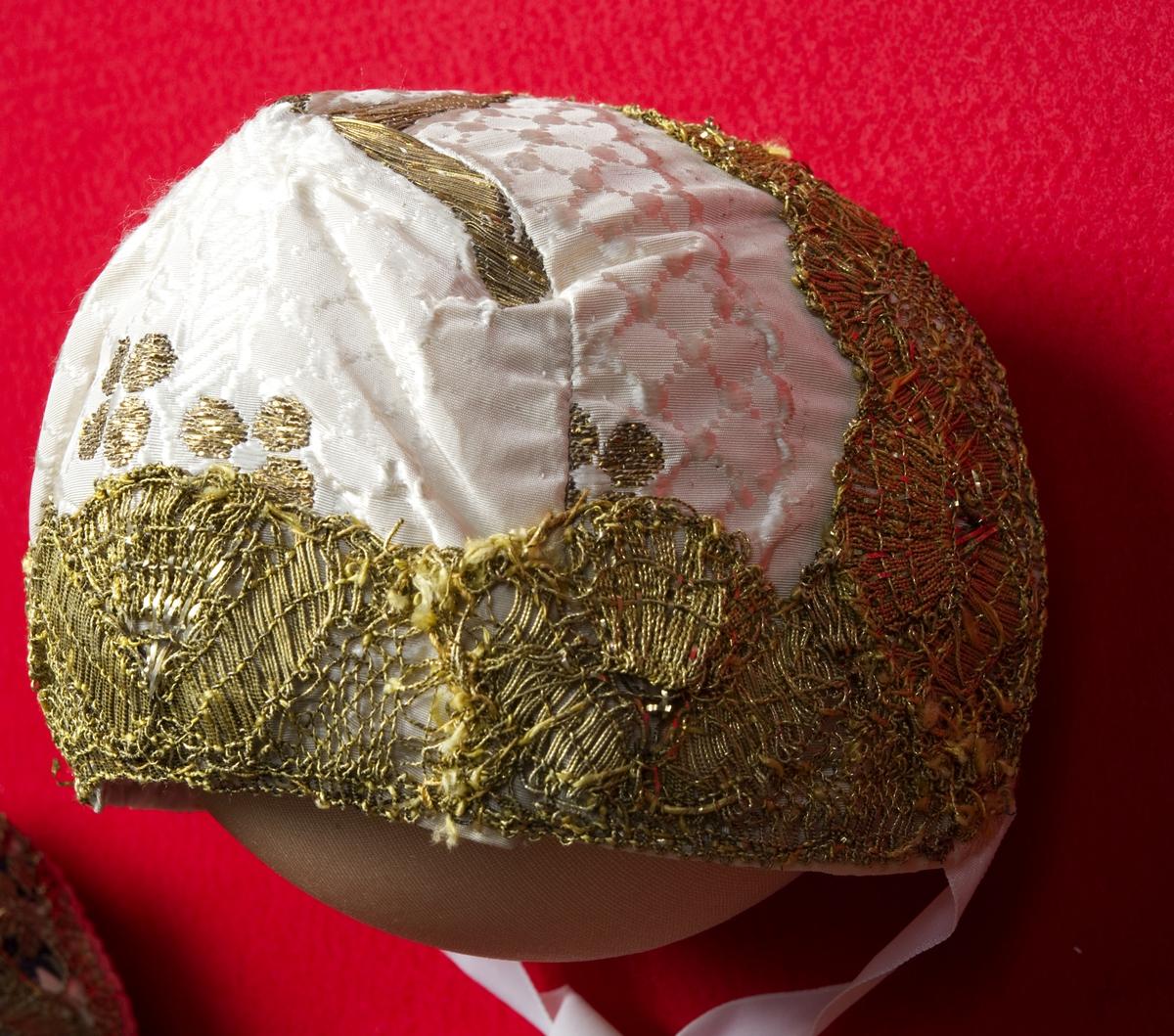 Hvit dåpslue i silke med dekor av kniplet blonde (metall). Rosa silketaft fôr, hvite knytebånd.