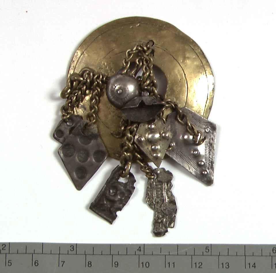 Rund, svakt konveks messingplate med hull i midten. Fastmonterte messinglenker med dekorative 8 sølvsmykker i endene som er punslet.