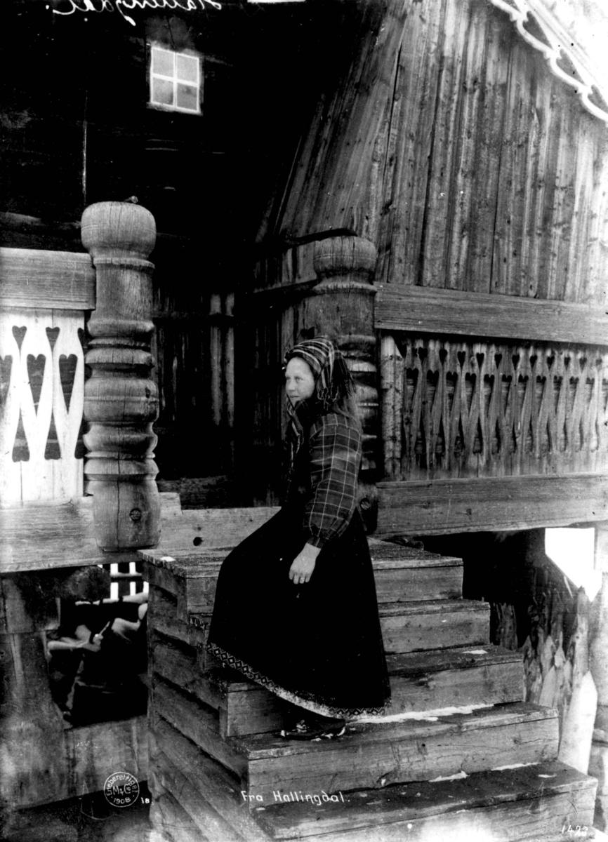 Hallingdrakt. Kvinne på trappa foran et hus.