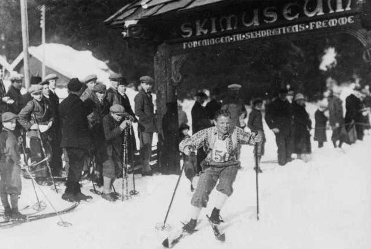 Holmenkollrenn. Deltaker nr. 50 passerer skilt for Skimuseet. Tilskuere langs løypa.