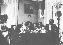 Mennesker rundt kaffebord, ant. Axel Q. Wiborg t.h., hans ko