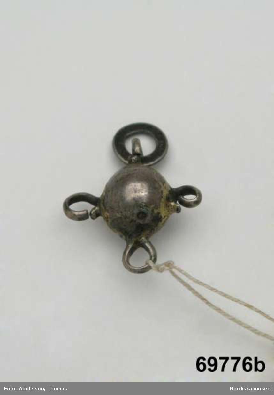 """Huvudliggaren: """"Halsband fr. Enontekis kapellförs., Torne lappmark, Finland. Från Nekkela. Af glaspärlor, med två silfverkläppar (l[apska:] silbboalloh) och en silfverplatta. Ink. af jägmästaren Hugo Samzelius. 1891. 3 löfhängen saknas på den större kläppen, 2 ringar saknas på den mindre kläppen. Bil. Samzelius 478."""""""